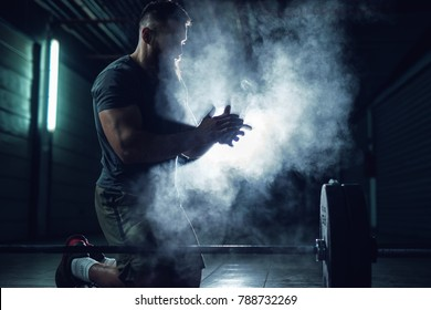Focussed hardworking active fitness strong muscular bearded bodybuilder man clapping hands with chalk powder before strength training with a heavyweight dumbbell in the underground garage.
