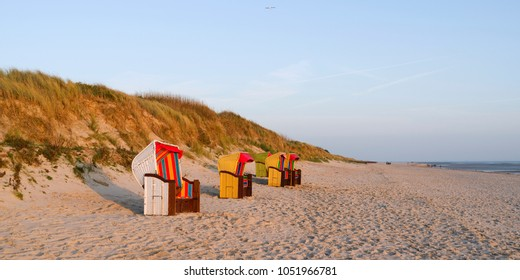 Foehr / Germany: Colorful empty hooded beach-chairs at Goting beach on the south coast of the Frisian island in the deep November afternoon sun