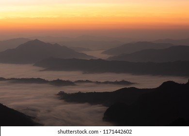 Fog among mountainn, yellow gradient sky at dawn