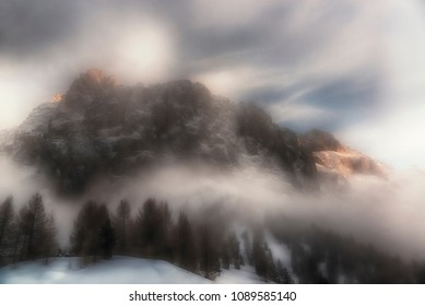Fog around the mountain Sella with last rays of Sun on the top in winter season and woods in foreground, Dolomites - Italy