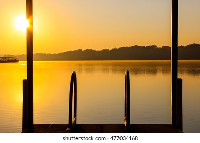 Fog covered lake at sunrise with view from dock; autumn background with copy space