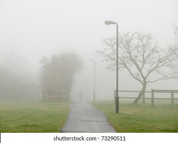 Fog covering a road in park. Unrecognizable man  walking from the mist.