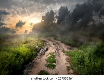 Fog and dirt over country road at sunset