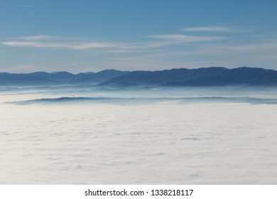 Fog filling a valley in Umbria (Italy), with layers of mountains and hills, various shades of blue