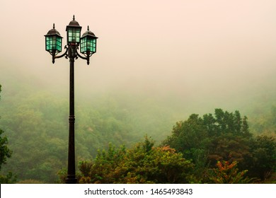 Fog. Landscape. Shows a single street lamp, lighting on a lantern mountainous terrain. Copy space.