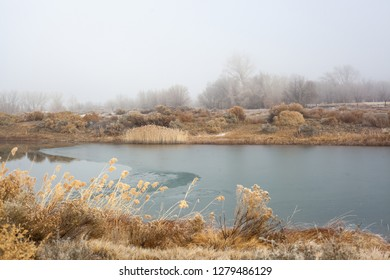 Fog lies on the far shore of a partially frozen lake in western Colorado on an early winter afternoon