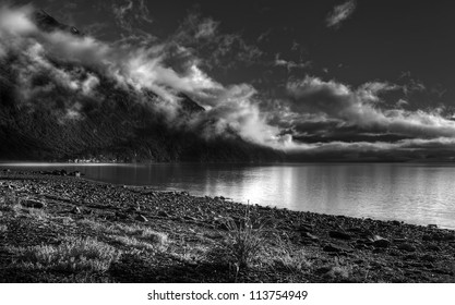 Fog lifting as the sun comes up on Whittier Beach in Alaska in black and white.
