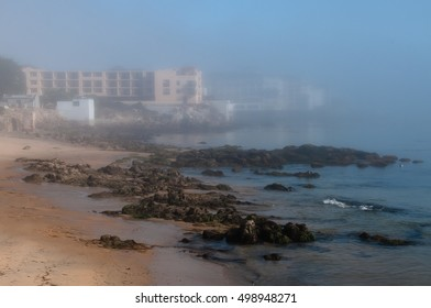 Fog lifts revealing beach, rocks and Cannery Row in the background, horizontal view.