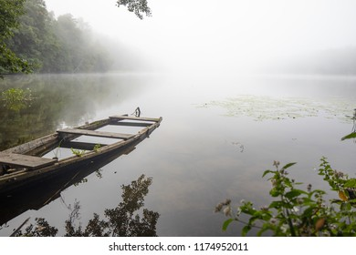Fog, mist or haze over a lake and a fishing boot. Colorful leaves and foggy skies with some white clouds. Masuria region, Poland.