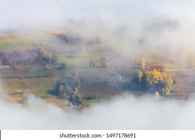 Fog in Mountains valley with colorful trees and farmland fields
