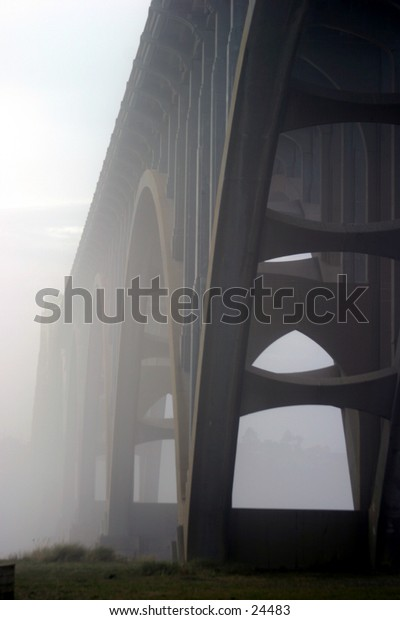 fog moves in and around a bridge in oregon