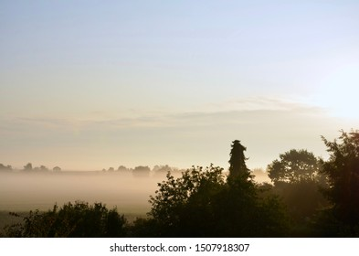 Fog on a frosty autumn morning in the countryside of Bavaria in Germany, trees in front, rime on the field behind, silhouette of forest in the background