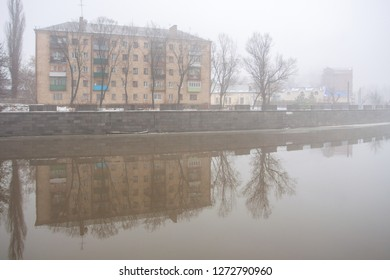 Fog on the river and on the embankment. Gray foggy wet day with poor visibility and clouds and an apartment building on the river embankment.