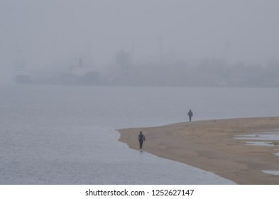 Fog on the river. People walk along the edge of the beach