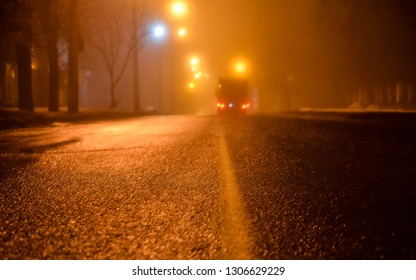 Fog on the streets of the night city. Asphalt road and car in fog. wet asphalt, dangerous slippery road in the winter season. Street lights. car rear lights. selective focus