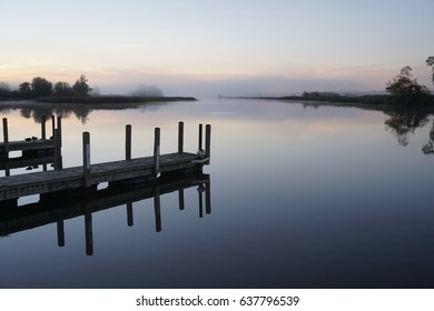 Fog over calm river with dock in foreground on cold October morning