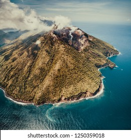 Fog over Indonesia volcano. Aerial drone shot. Amazing overview of Indonesian land surrounded by the ocean. Asian landscape. Active volcano among the calm blue ocean water. Cloudy sky background.