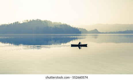 Fog over the lake. In calm water reflection mirror. Man with a paddle in the boat.