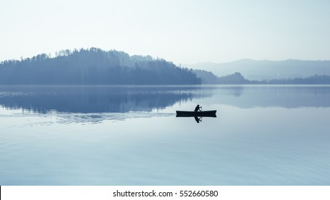 Fog over the lake. In calm water reflection mirror. Man with a paddle in the boat. Black and White.