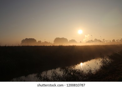 Fog over the meadows colored by the sun and shadows by trees during sunrise in Nieuwerkerk aan den IJssel in the Netherlands.