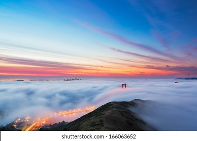 Fog pours into the bay and over the Golden Gate Bridge as sunrise lights the clouds over San Francisco, California.