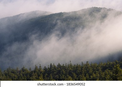 Fog rolling over a ridgeline of Mount Monadnock on an early autumn morning in New Hampshire