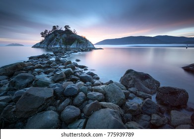 Fog rolls into Whytecliff Park at sunset producing some vibrant beauty on the Salish Sea in Howe Sound West Vancouver BC Canada.