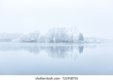 "Fogg, ice and frozen harbour trees over the citylake ""the Nieuwe Meer"" in Amsterdam the Netherlands."