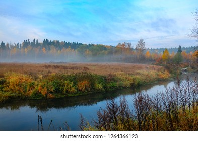 Foggy autumn landscape with small forest river.Autumnal hazy early morning.Twilight.Calm stream of river flowing between the woods and meadows covered by fog.Windless weather at sunrise.