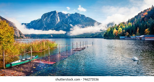 Foggy autumn scene of Altausseer See lake. Sunny morning panorama of Altaussee village, district of Liezen in Styria, Austria. Beauty of countryside concept background.