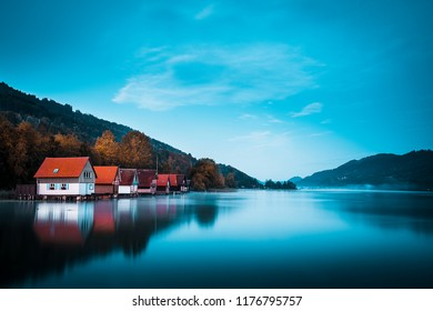 Foggy autumn sunrise over a lake with old wooden boat houses near Immenstadt in Germany