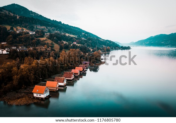 Foggy autumn sunrise over a lake with old wooden boat houses near Immenstadt in Germany. Photograph taken by a drone to show the wooden houses from above.