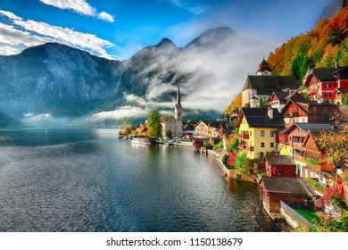 Foggy autumnal sunrise at famous Hallstatt lakeside town reflecting in Hallstattersee lake. Location: resort village Hallstatt, Salzkammergut region, Austria, Alps. Europe.