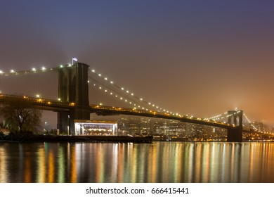 Foggy Brooklyn bridge and reflection of city light on the East river, New York City