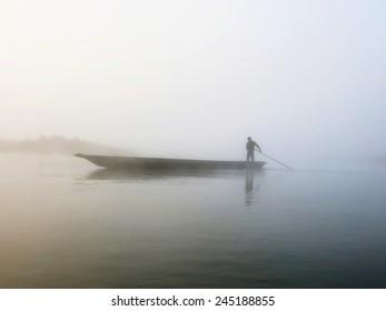Foggy dawn in Chitwan. Morning on the river in canoe