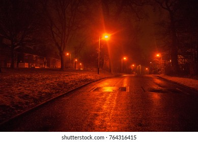 Foggy Empty Street Illuminated by Red Light Road Lamps in Snowy and Cold Winter Night. Snow Wet Misty Deserted Road at Night in Residential Silent Shut Houses as Scary Mysterious Haunting Background