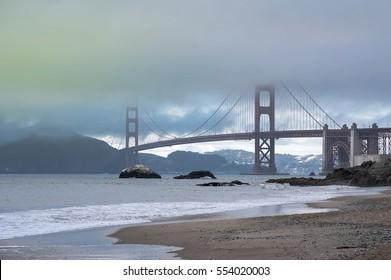 Foggy evening at Baker Beach near famous San Francisco's Golden Gate Bridge