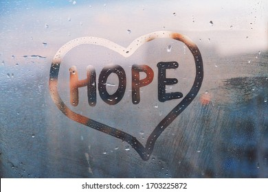 Foggy glass on window with written finger word yellow color Hope in paint heart concept photo with copy space on blue and warm background