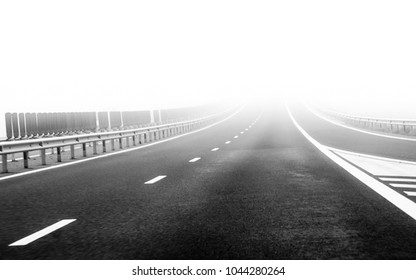 Foggy gray asphalt speedway road landscape photography background. Car driving into de mist on a bad weather winter day. The highway is in fog with very limited perspective for the drivers