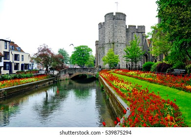 Foggy landscape of Canterbury with blooming tulips, traditional houses by the canal and old tower in England