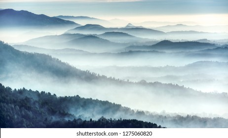 Foggy landscape on the hills in a winter cold morning seen from the mountains near the city of Varese