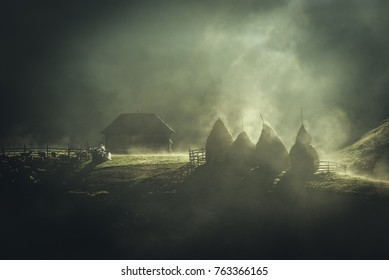 Foggy morning in the Carpathian mountains, romania. Traditional Romanian house with hay bales and fog.