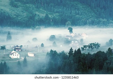 Foggy morning mountain summer landscape with mist and village