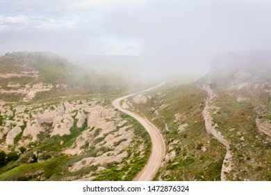 foggy morning over a windy road and rock outcropping in western Nebraska - aerial view