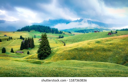 Foggy morning scene of Compaccio village, Seiser Alm or Alpe di Siusi location, Bolzano province, South Tyrol, Italy, Europe. Picturesque summer view of Dolomiti Alps.