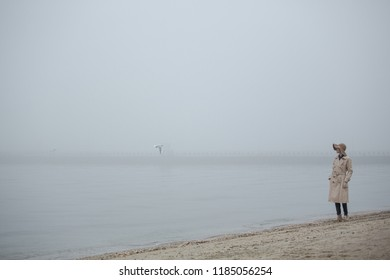 Foggy morning at sea. Woman in hat and coat walking on autumn beach