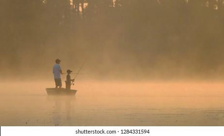 Foggy morning sunrise on lake, father and son fishing.