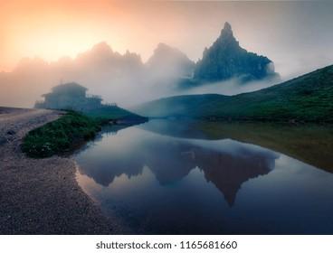 Foggy morning view of Baita Segantini mountain refuge with Cimon della Pala peak. Fantastic summer sunrise in Dolomiti Alps, Rolle pass, Trentino province, Italy, Europe.