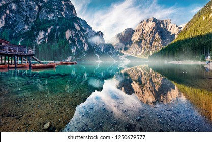 Foggy morning view of Braies (Pragser Wildsee) lake. Majestic summer sunrise in Fanes-Sennes-Braies national park, Dolomiti Alps, South Tyrol, Italy, Europe. Beauty of nature concept background.