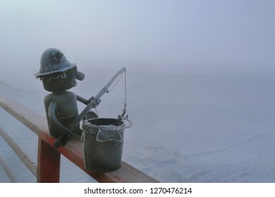 foggy morning in winter, snowfield, metal craftwork of toy fisherman covered with hoarfrost, art work by unknown local of Listvjanka community in Irkutsk region of Russia, free of copyright protection